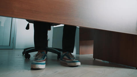 Unrecognisable office worker stomping legs in sneakers under table Live Action