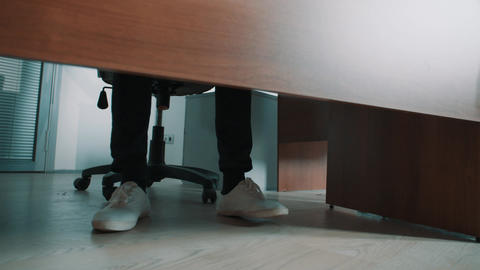 Unrecognisable office clerk stomping legs in sneakers under table Live Action