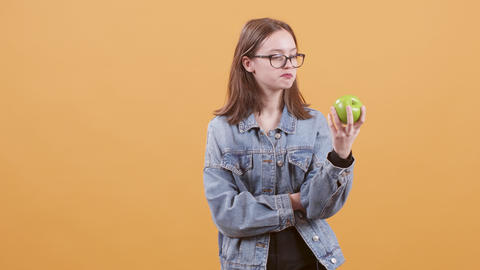 Teenage girl hold an apple in her hand and promotes healthy eating Footage
