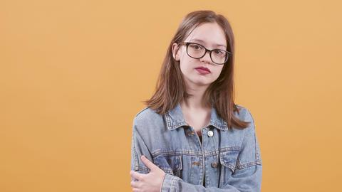 Teenage girl in eyeglasses and blue denim jacket nods her head as approval Live Action