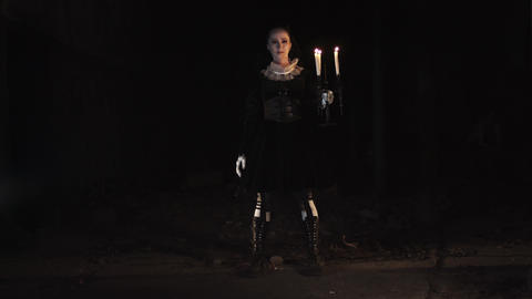 Woman in victorian style dress standing in dark room with candelabrum Footage