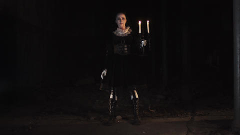 Woman in victorian style dress saluting in dark room with candelabrum Footage
