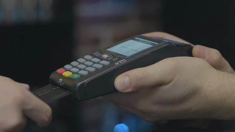Credit card machine for money transaction. Man hand with credit card swipe Footage