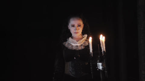 Mystical woman in victorian dress standing in dark room with candelabrum Footage