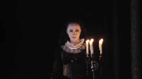 Mystical woman in victorian dress staring in dark room with candelabrum Footage