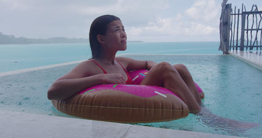 Vacation rain - funny video of woman on donut float in luxury pool Footage