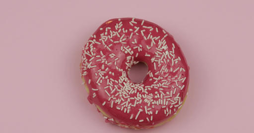 Sweet donut rotating on pink background. Top view. Tasty, fresh sprinkled donut Footage