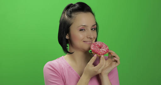 Beautiful young woman with great pleasure eats a donut. Chroma key Footage