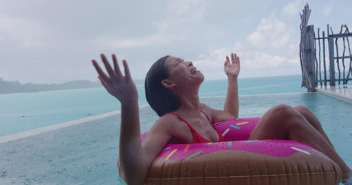 Rain on vacation - funny video of woman unhappy on donut float in luxury pool Footage
