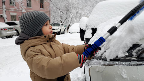 4k video of toddler boy cleaning car from snow with brush Child helping cleaning Live Action