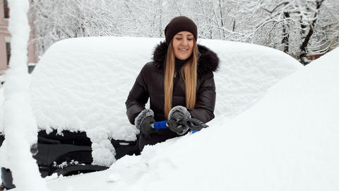 4k footage of beautiful smiling young woman removing snow from her automobile Live Action