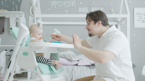 Caring dad with cellphone feeding infant bsaby Live Action