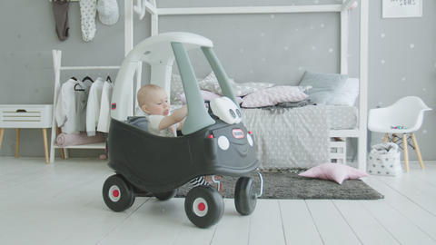 Cute infant playing in baby car in domestic imterior Footage