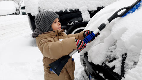 4k video of 3 years old toddler boy helping cleaning car covered in snow after Footage