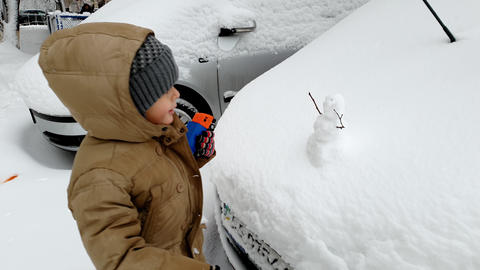 4k footage of little boy looking at small snowman on the car hood Footage