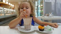 A cute little girl drinks cappuccino Archivo