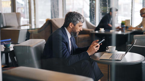 Middle aged entrepreneur using smartphone touching screen sitting in cafe alone Footage