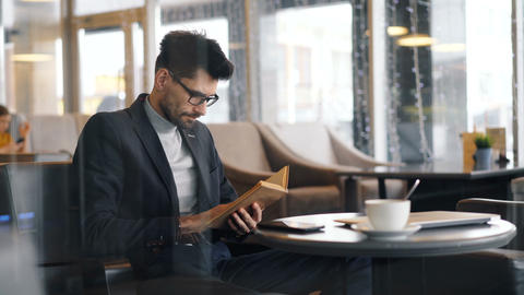 Entrepreneur focused on reading book sitting in cafe waiting for meeting Footage