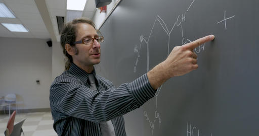 Man in his 40s giving a lecture on organic chemistry pointing to a formula on a blackboard in a high Live Action