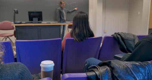 [alt video] Young woman drinking from a togo coffee cup in a college...