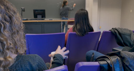 Young woman drinking from a togo coffee cup in a college classroom during a chemistry lecture with a GIF
