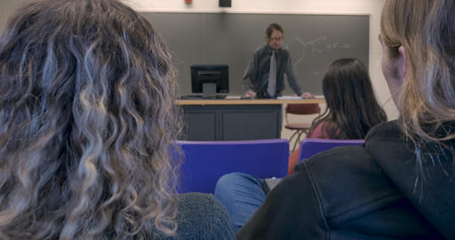 A distracted male and female student talking to each other during a chemistry lecture in a high Live Action