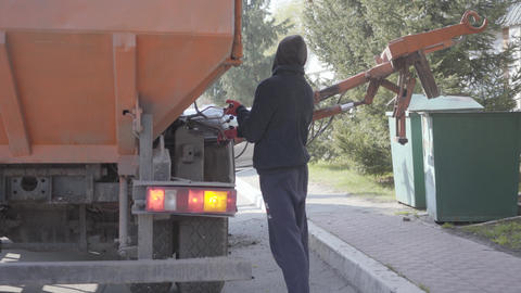Back view of the man controlling garbage machine work. The worker in casual Footage