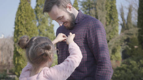 Cute daughter buttoning her smiling dad's button on a plaid shirt on the Live Action