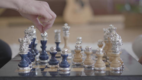 Two people playing beautiful luxury chess in the living room in a cozy Footage