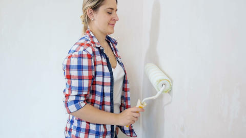 Beautiful young woman renovaating her new apartment. Young girl painting walls Footage