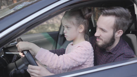 Little girl sitting on father's lap in the car close up. The child is learning Footage