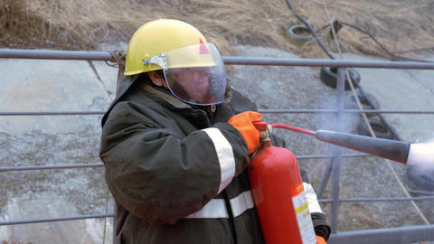 Woman fireman in protective helmet and uniform extinguishes flame with Footage
