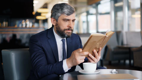 Smart entrepreneur reading book sitting in cafe alone enjoying interesting story Footage