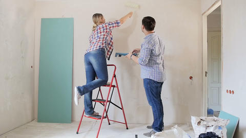 Video of happy young couple painting walls with paint roller in their new Footage