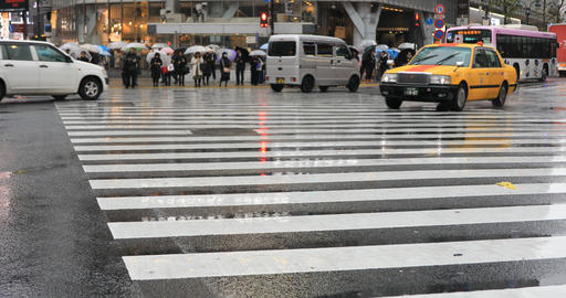 Moving cars and walking people at Shibuya crossing in Tokyo rainy day ビデオ