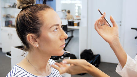 Closeup 4k footage of fashion models face while professional makeup artist Footage