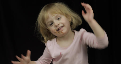 Child with dirty face from melted chocolate and whipped cream smiling Footage