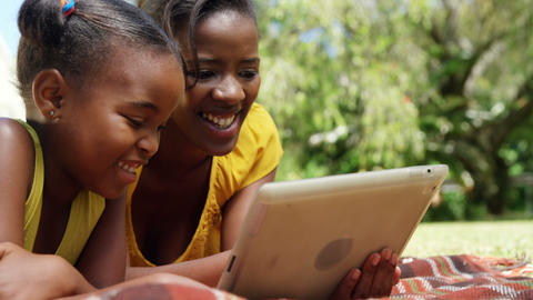 Portrait of cute mother and daughter are using a tablet in the garden Live Action