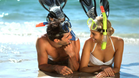 Young couple wearing diving mask lying on beach Live Action