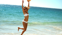 Young woman jumping on beach Live Action