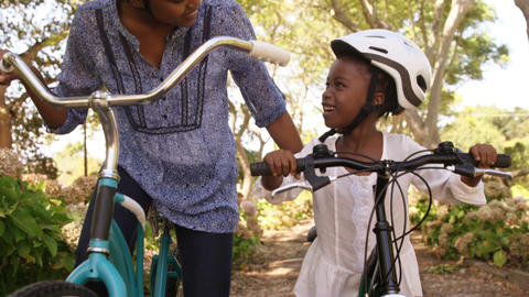Mother and daughter are preparing to riding bike Live Action