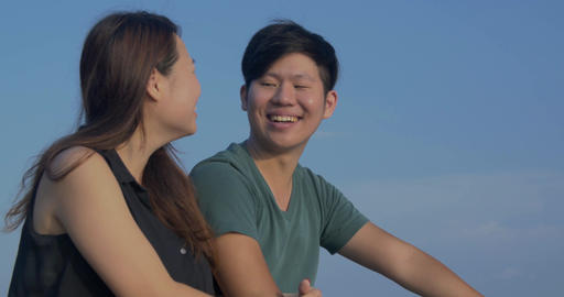 Close up Taiwanese couple laughing on date together beautiful scenic blue sky ba ビデオ