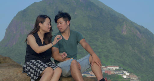 Young Asian couple sitting in beautiful location relaxed on rocks near ocean ビデオ