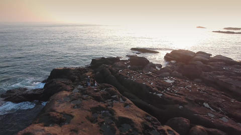 Young Active couple walking along rocks on seaside at sunrise in Taiwan Aerial S Footage