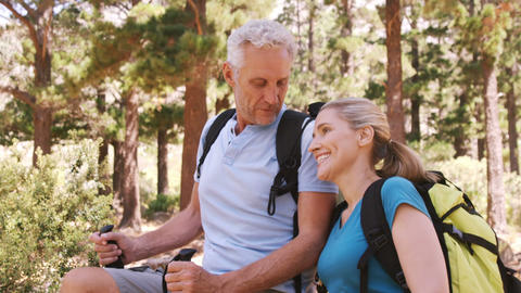 Hiker couple standing with hiking poles Live Action