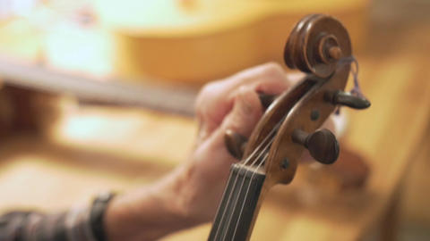 Old Retired Luthier Man Hands Tuning Violin Closeup Footage