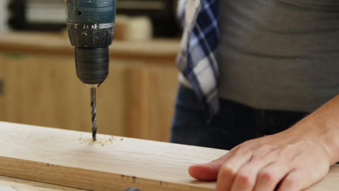 Focus on carpenter drilling a wooden plank Live Action