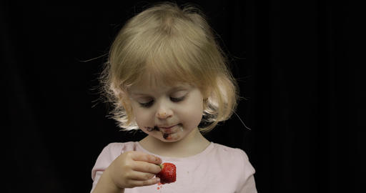 Child with dirty face from melted chocolate and whipped cream eats strawberry Footage