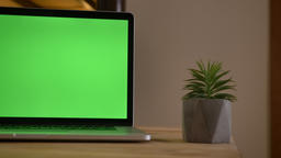 Closeup shoot of a green chroma screen of the laptop lying on the desk next to Footage