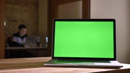 Closeup shoot of green screen of the laptop laying on the desk in office indoors Footage